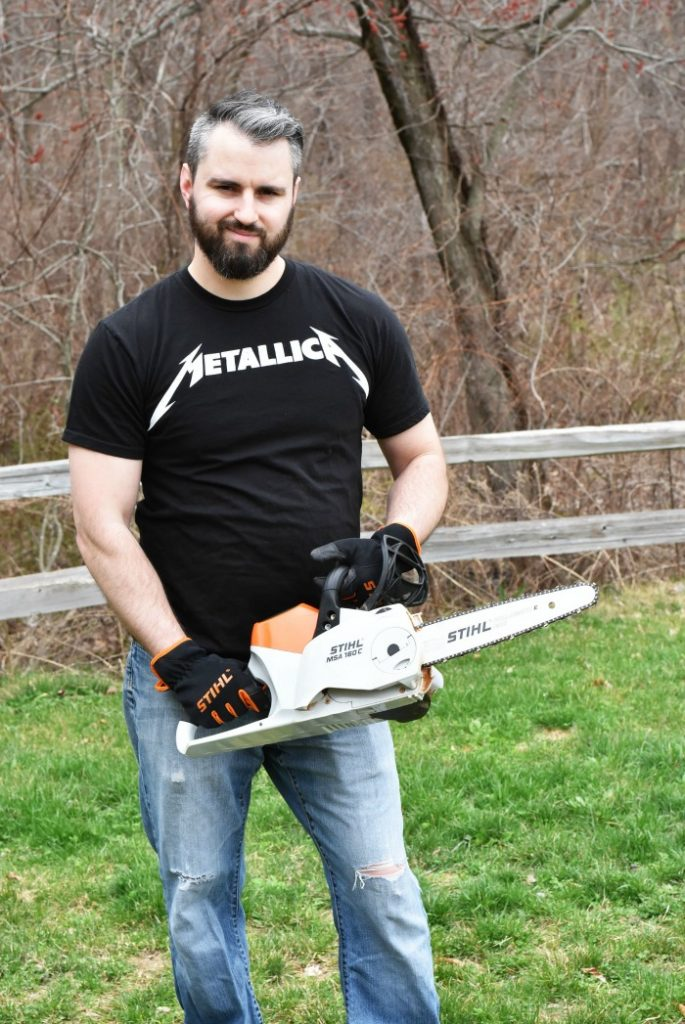 man holding battery powered Stihl chainsaw