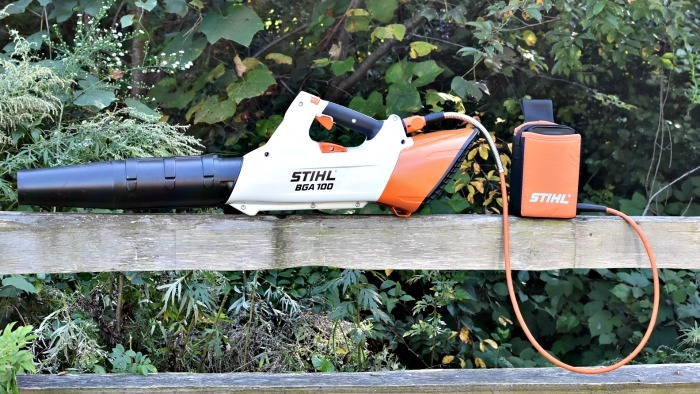 Stihl BGA 100 Battery Blower sitting on fence rail with woods in the background.