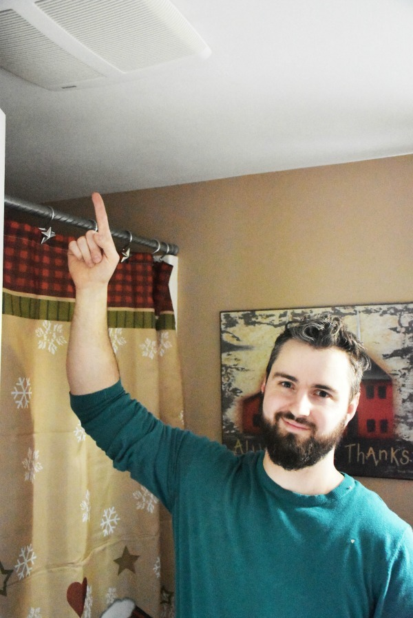 man pointing at new bathroom exhaust fan in ceiling