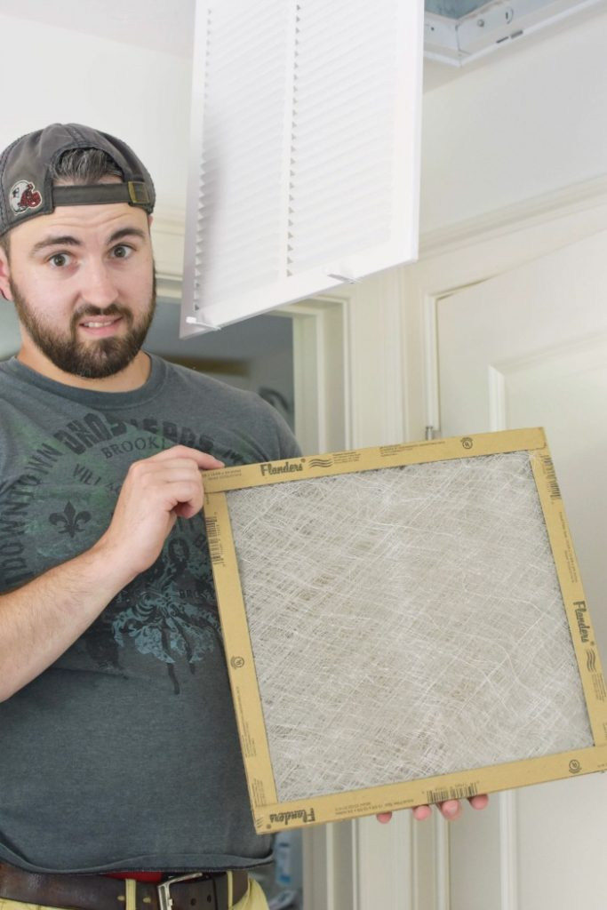 man holding dirty air filter