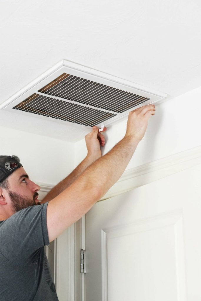 man opening return air vent in ceiling