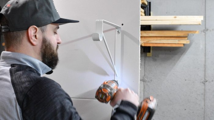 man screwing in a shelf bracket to a wall