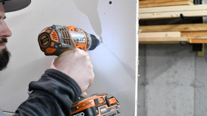 man screwing a screw into a wall with a hand drill