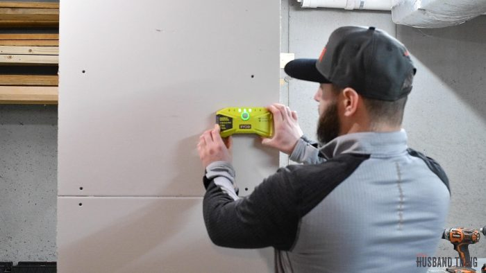 man using a stud finder on wall