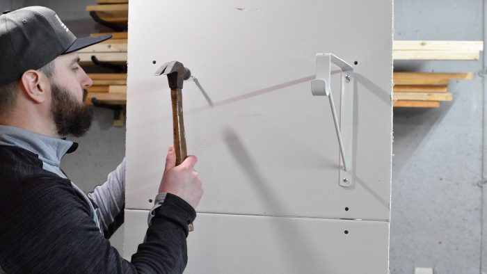 man hammering a wall anchor into a wall