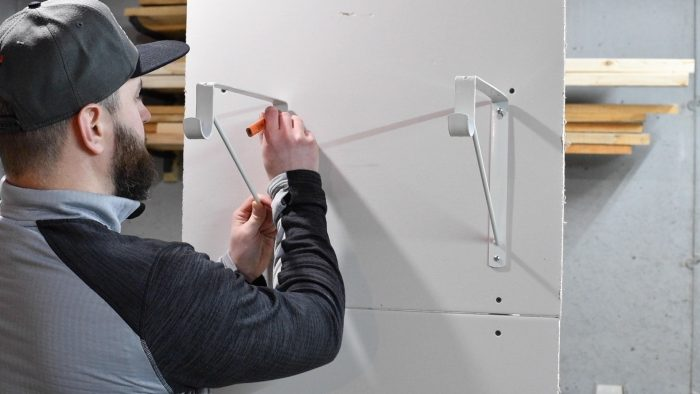 man marking the hole of a shelf bracket to the wall with a pencil