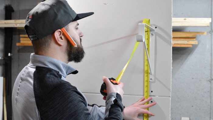 man measuring the top of a shelf bracket from the floor with a tape measure