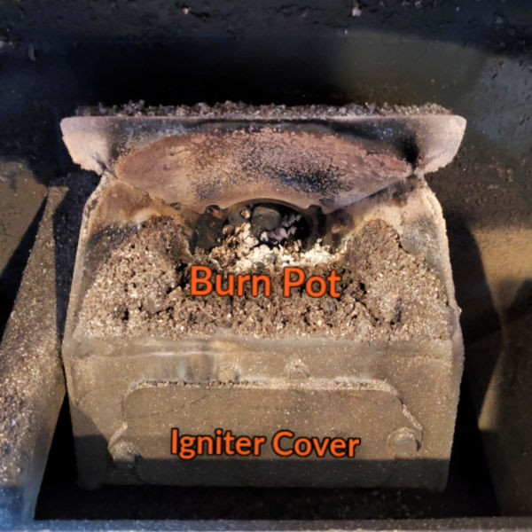 image of a pellet stove burn pot and the igniter cover below. Ash is inside the burn pot