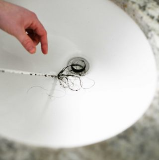 unclogging a bathroom sink drain with a barbed tool. Hair on the tool