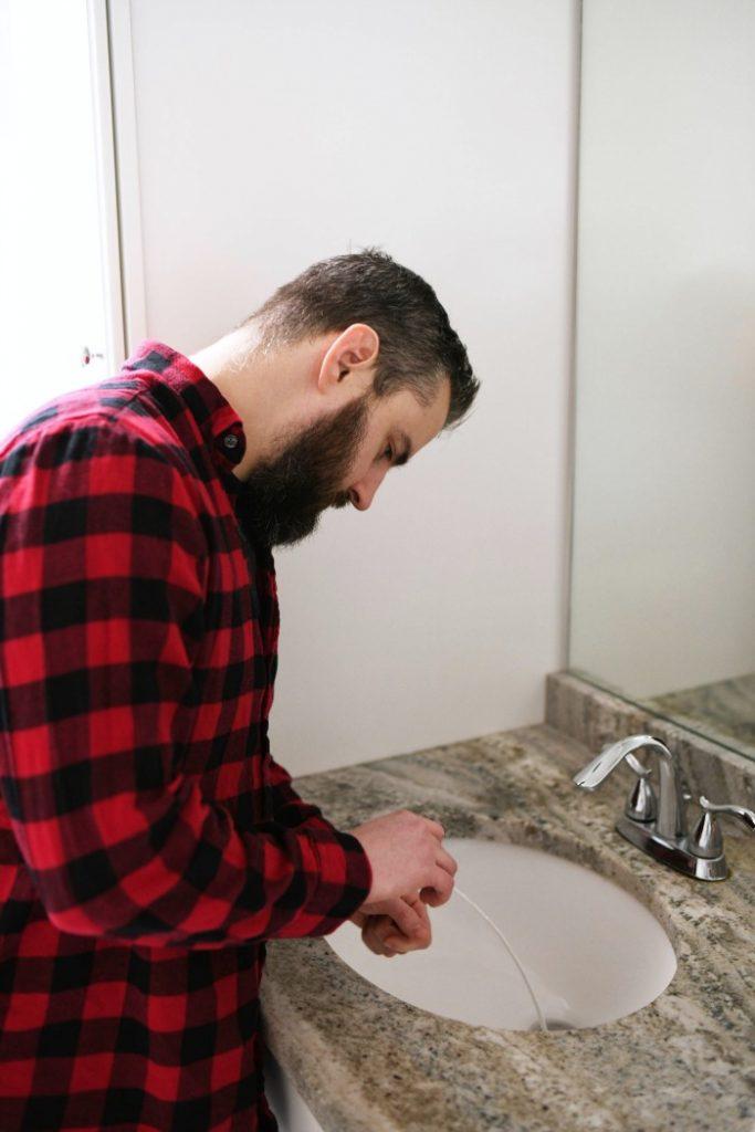 man sticking drain cleaning tool into bathroom sink drain