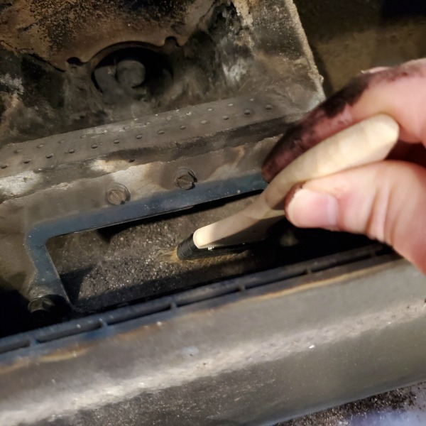 using a chip brush to sweep ash out of the igniter cavity.