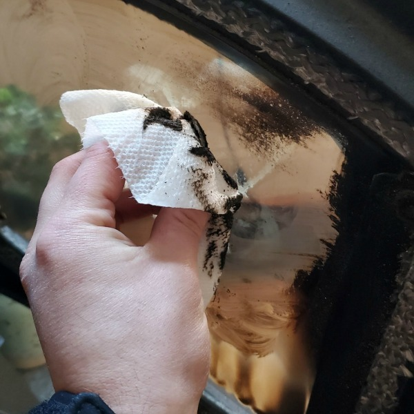 hand holding wet paper towel, wiping the inside glass of a pellet stove. glass is coated with black carbon deposits from fire.