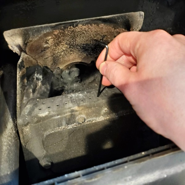 sticking a small allen wrench into one of the holes in a pellet stove burn pot grate
