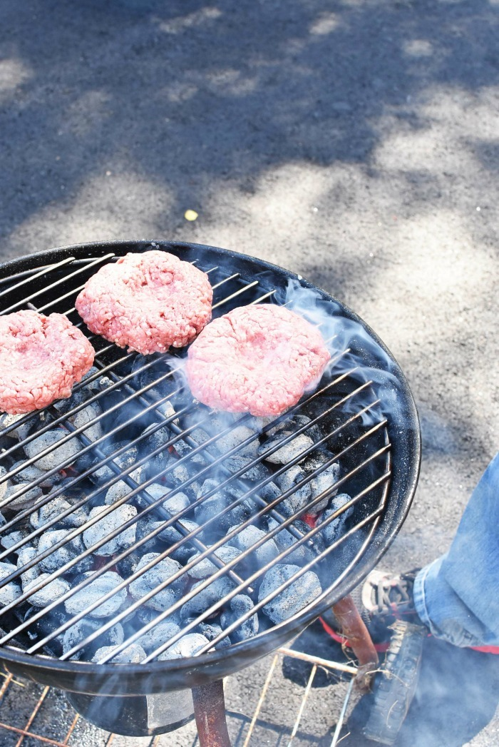 hamburger patties on a charcoal grill