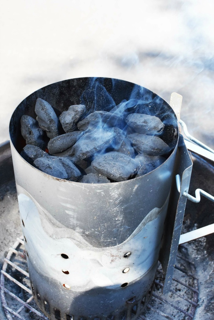 charcoal briquettes smoking inside of a chimney