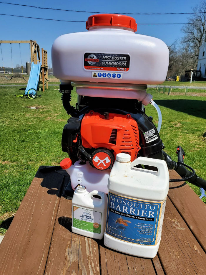 gas backpack sprayer and chemicals on bench